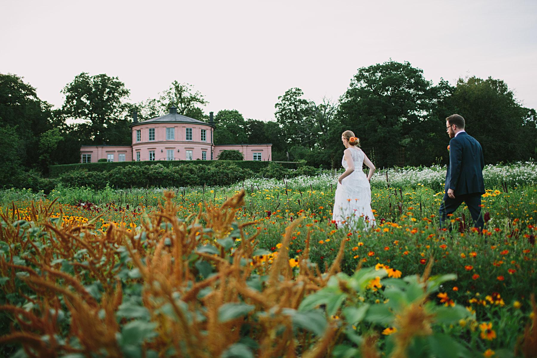 brudparet går genom blomsterängen vid rosendal