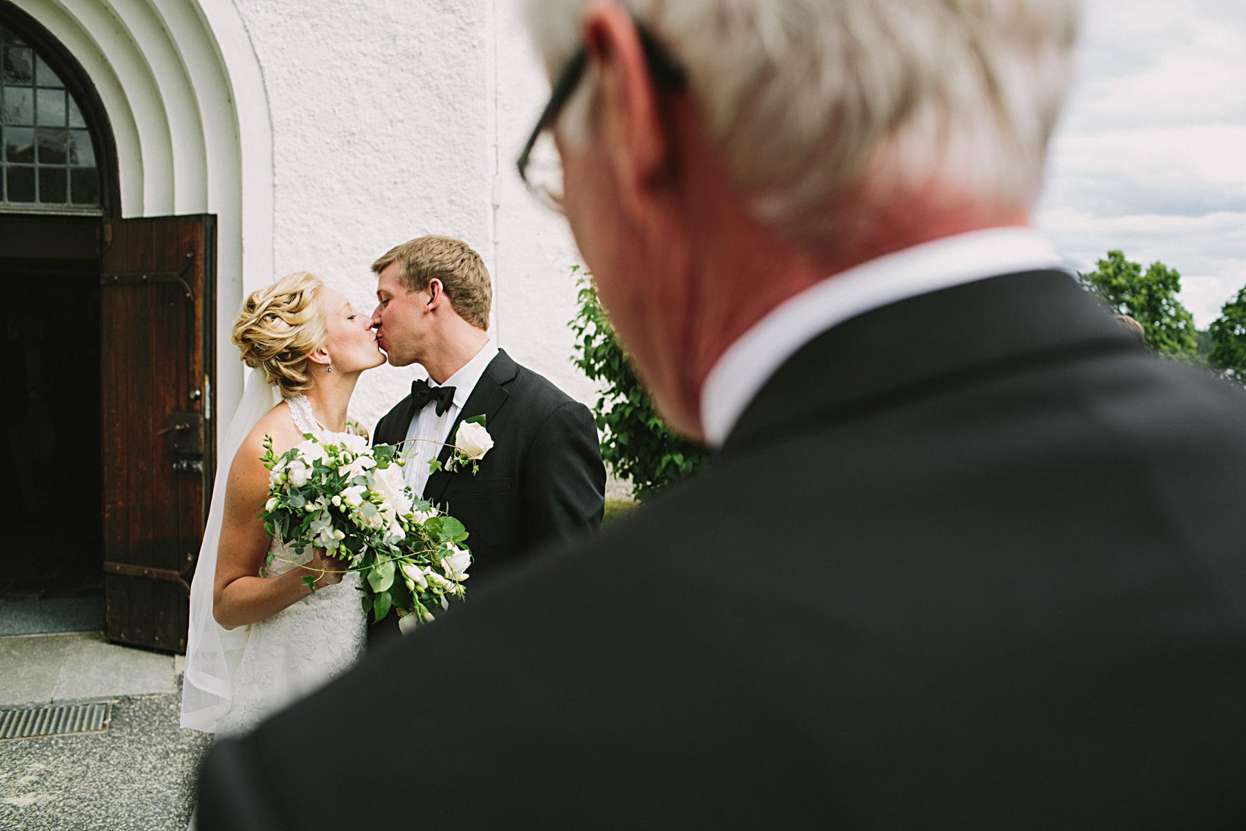 Brudparet kysser varandra framför kyrkporten