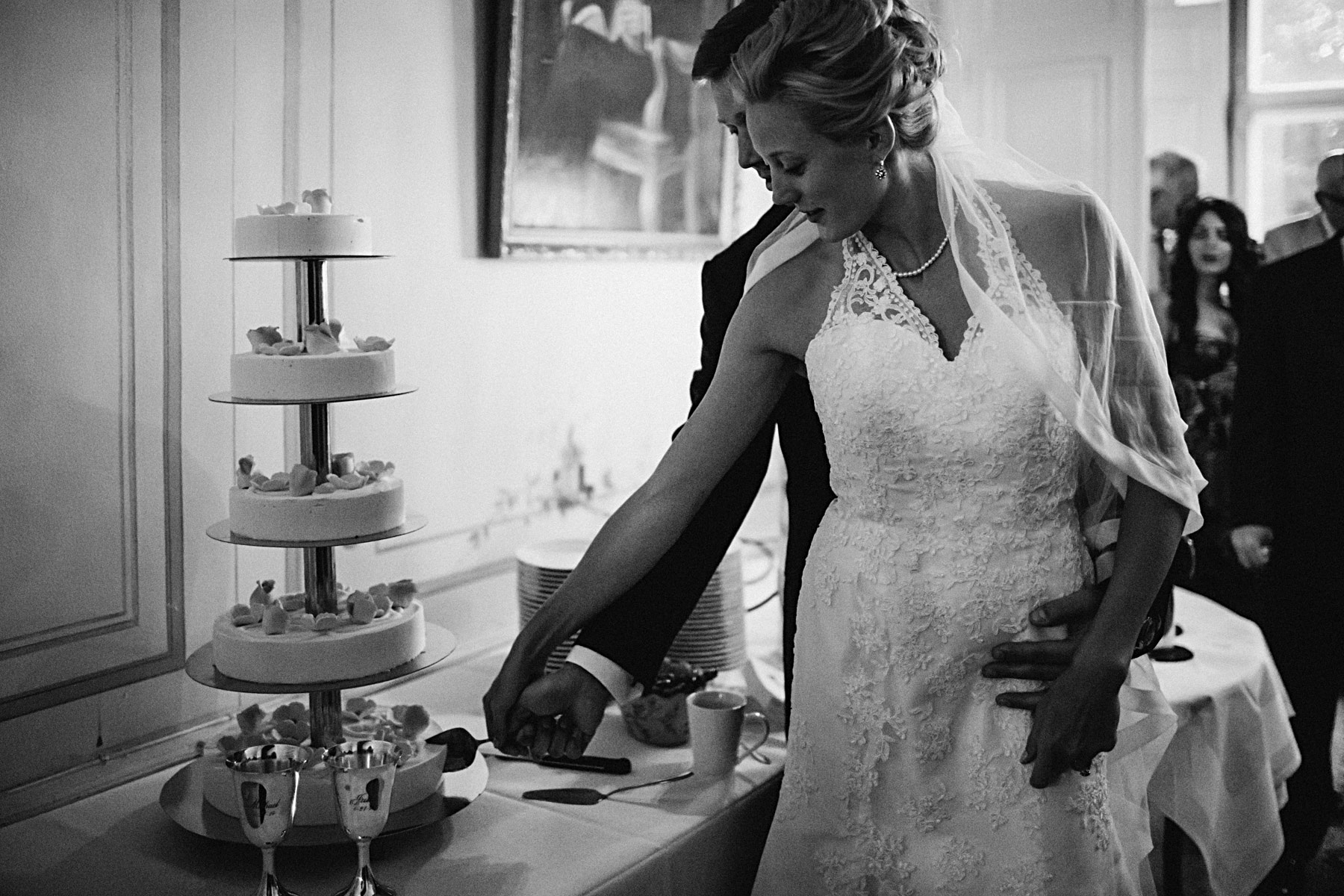 Brudparet skär tårtan med fem våningar med silverbägare fram