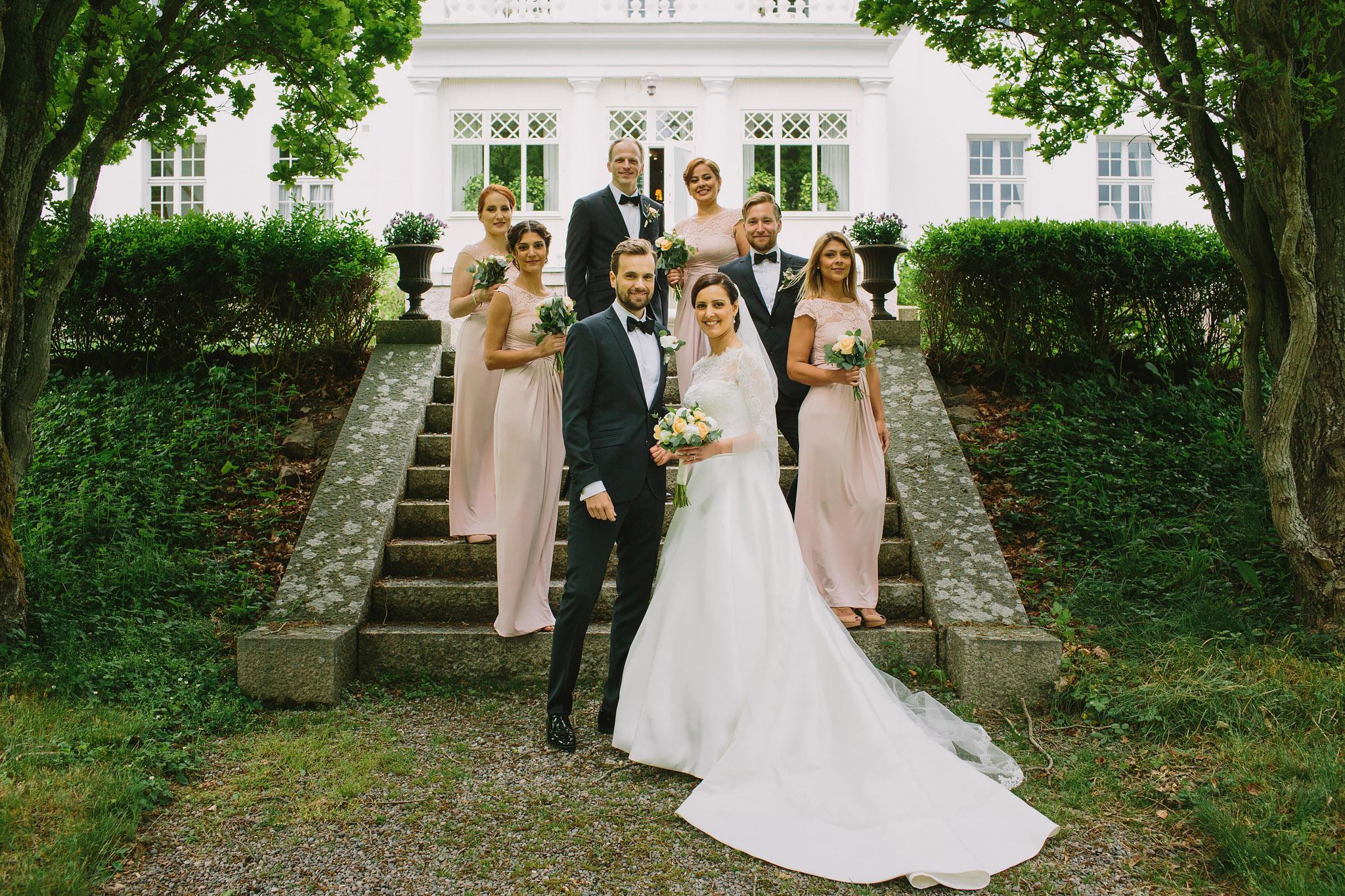 gruppfoto med brudföljet vid trappan på Bergendal