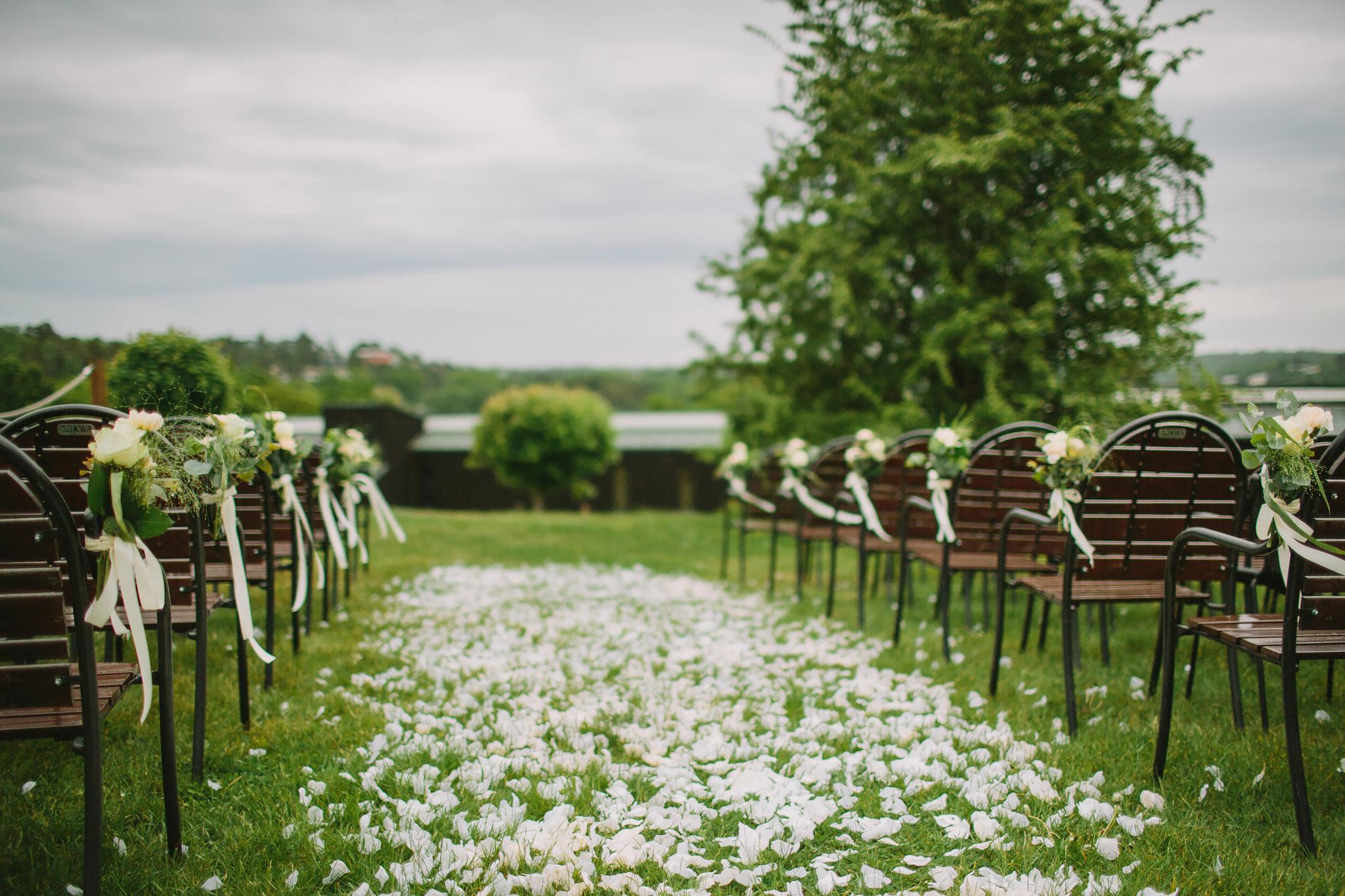 Blommor fästa på stolar inför utomhusvigsel
