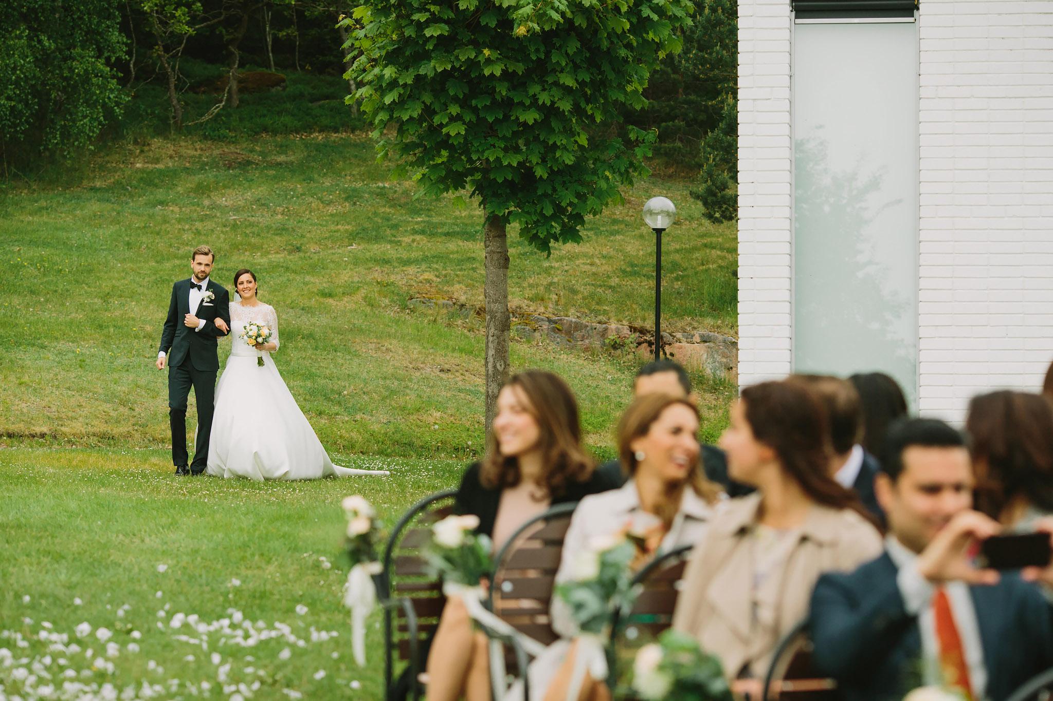 Brudparet marscherar in över gräset på utomhusvigsel