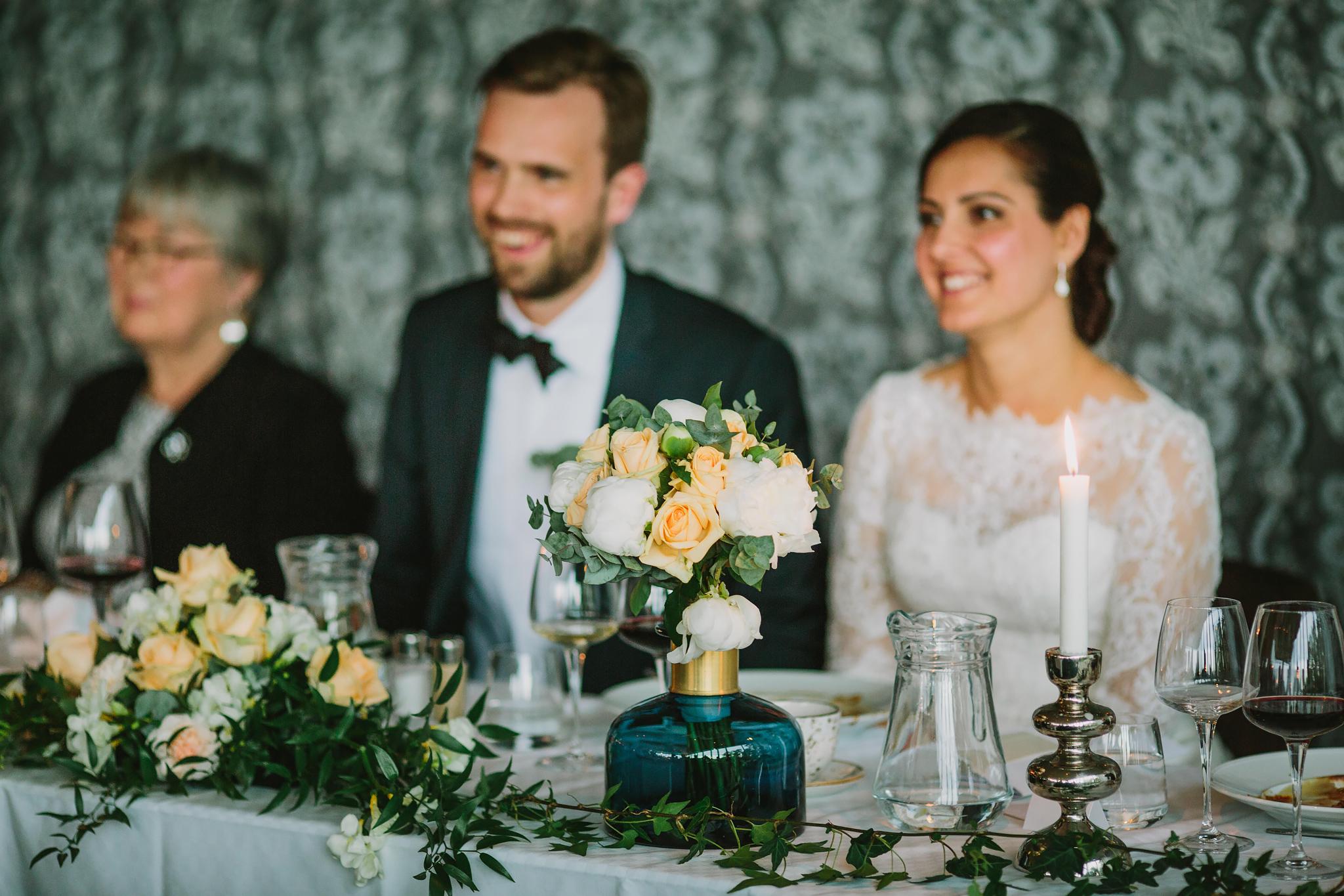 brudbukett mellan paret på bordet under bröllop